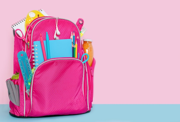Backpack with school supplies standing on pink background. copy space.