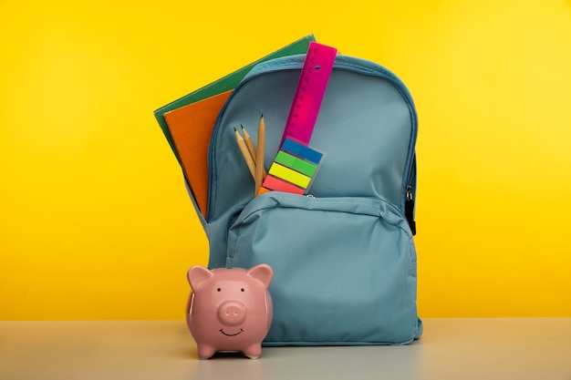 Backpack with school tools and piggy bank on yellow background