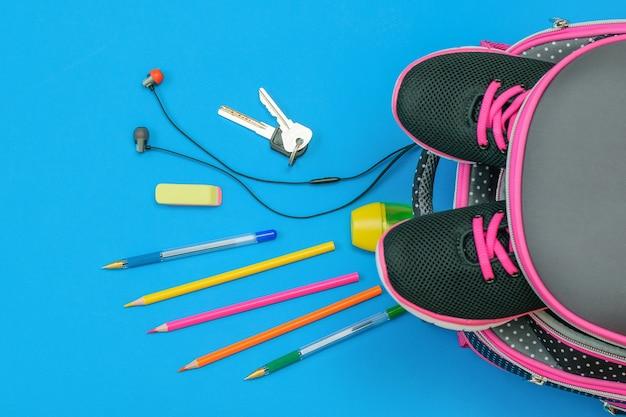 Рюкзак с кроссовки и разбросанные школьные принадлежности и ключи от дома на синем столе. квартира лежала. вид сверху.