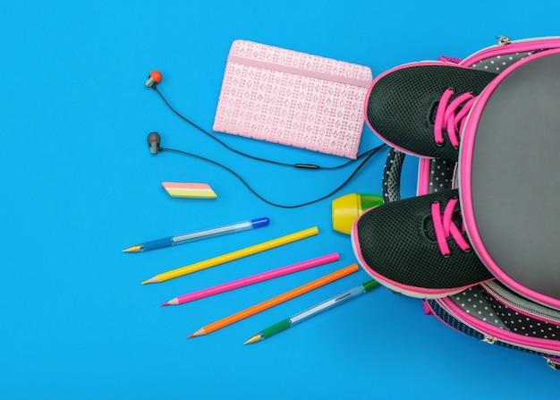 スニーカーと青色の背景に散在する学校付属品のバックパック。フラット横たわっていた。上面図。