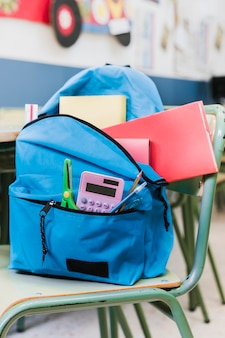 Backpack with stationery on chair