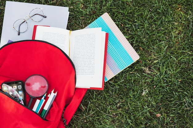 Backpack with stationery stuff on green grass