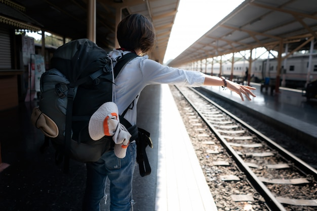 Backpack with traveler at the train station.  travel concept.