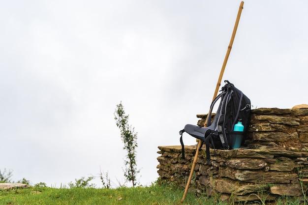 割れ目の近くの石の柵に水筒と竹の棒が付いたバックパック。山は雲に隠れています。ハイキングやトレッキングのコンセプト。