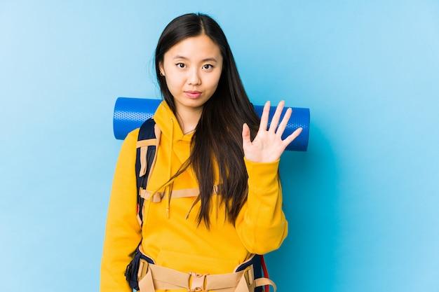 Показ молодой женщины китайского backpacker усмехаясь жизнерадостный 5 с пальцами.