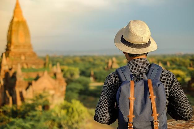 Молодой человек путешествуя backpacker с шляпой, азиатский путешественник стоя на пагоде и смотря красивые древние храмы, ориентир ориентир и популярный для туристических достопримечательностей в bagan, myanmar. азия трэвел концепция