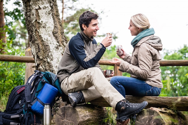 Backpacker couple taking rest aside hiking trail