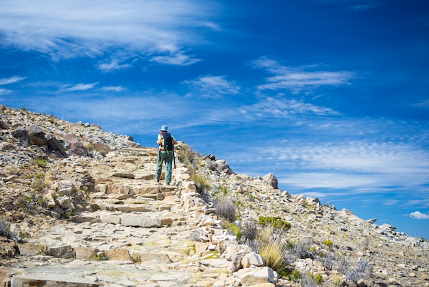 Backpacker exploring the majestic inca trails on island of the sun, titicaca lake, among the most scenic travel destination in bolivia. travel adventures and vacations in the americas.