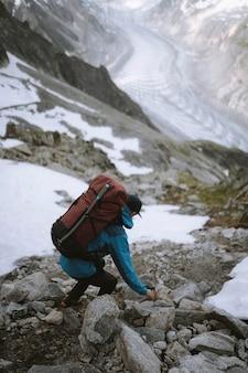 Backpacker hiking down chamonix alps in france