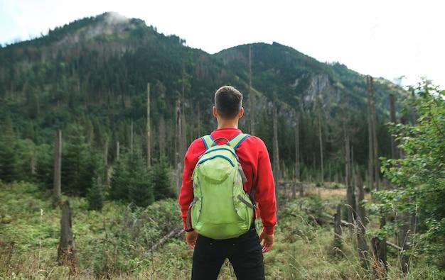 国立保護区の手つかずの自然を背景に立っているバックパッカーハイキング