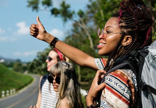 Группа разнообразных backpacker женщина hitch походы на стороне улицы