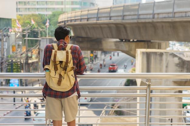 Backpacker is looking along road at a train station in bangkok