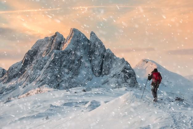 Альпинист backpacker, походы на снежный холм с величественной горой со снегопадом утром. пик сегла, норвегия