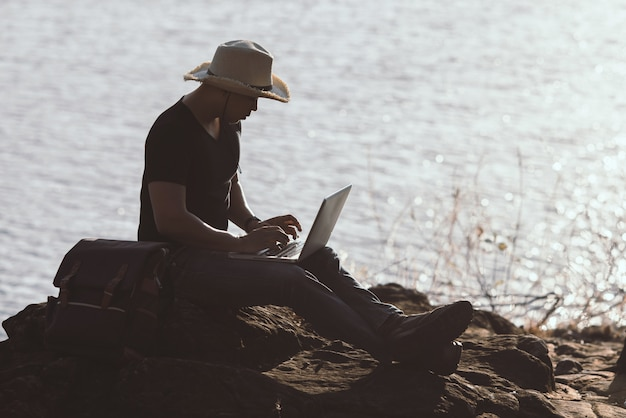 Backpacker relax on the mountain with using laptop