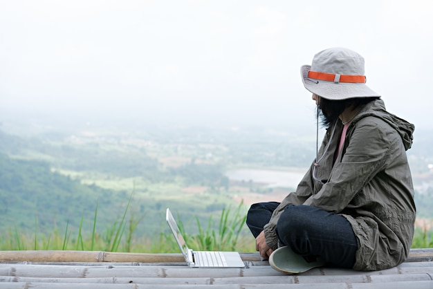Backpacker отдыхать на природе и использовать ноутбук для общения