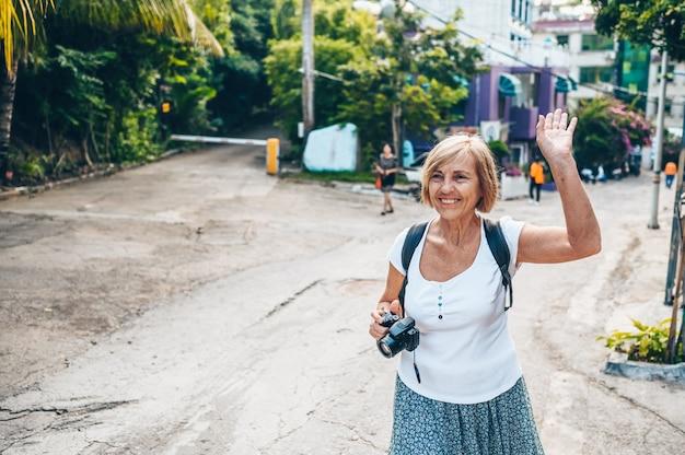 Наслаждаться пожилого старшего азиатского путешествуя туриста зрелой женщины backpacker идя фотографирующ в улице sanya местной напольной. путешествие по азии, концепция активного образа жизни. открывая хайнань, китай