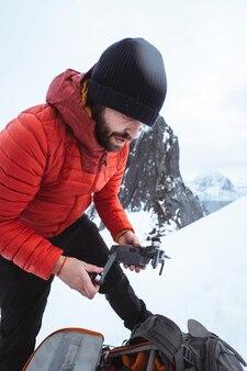 노르웨이의 눈 덮인 segla 산에서 드론을 설정하는 배낭 여행자
