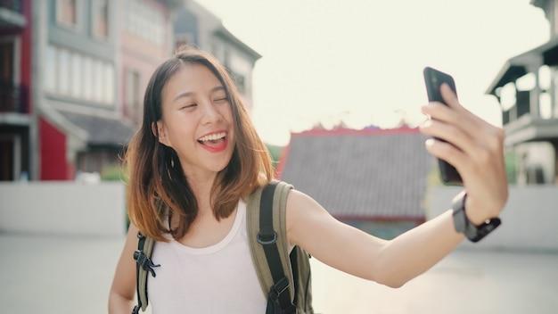 Жизнерадостная красивая молодая азиатская женщина блоггера backpacker используя smartphone принимая selfie