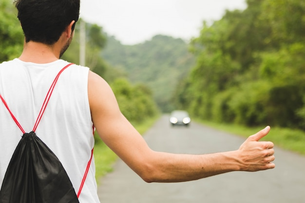 Backpacker tourist hitchhiking on mountain road in vietnam