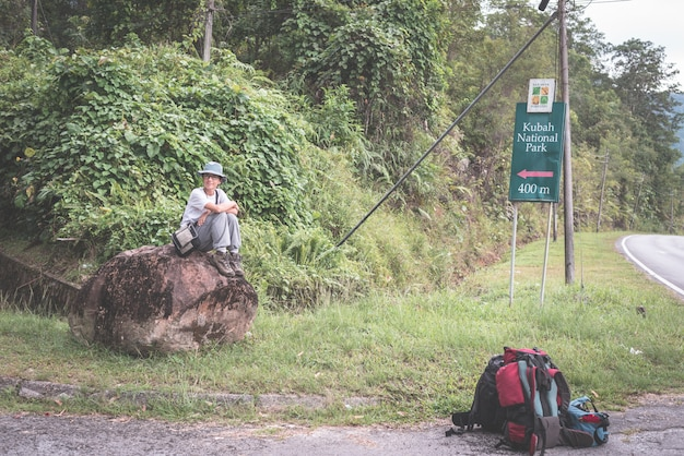 Backpacker waiting for hitchhike on the road for kubah national park, sarawak, borneo, malaysia.