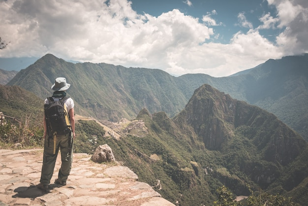 Backpacker walking on the inca trail above machu picchu, the most visited travel destination in peru