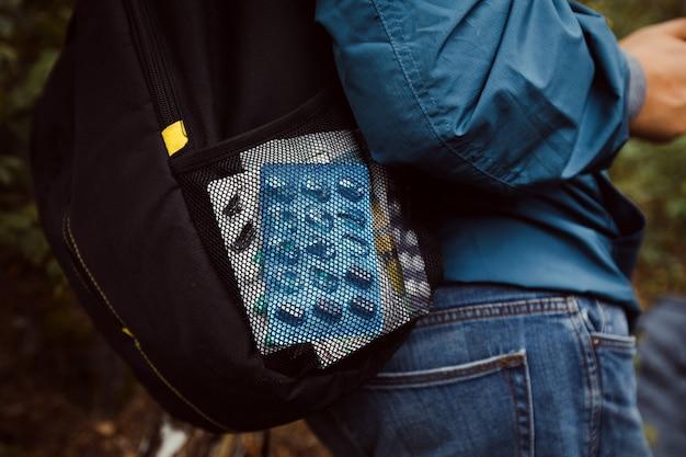 旅行中のタブレットと薬を使ったバックパッカー