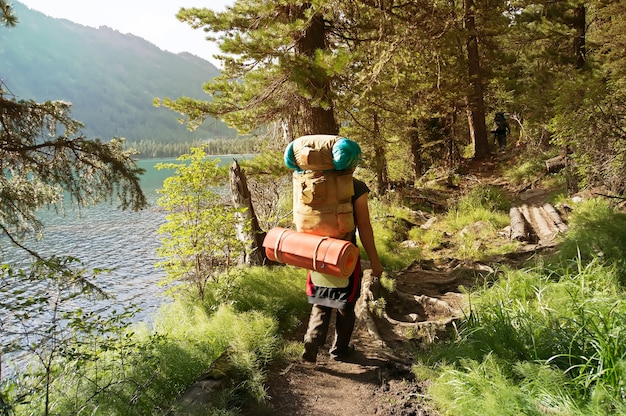 A backpacker with a large backpack. group of travelers with backpacks walk along a trail towards a mountain ridge.backpackers style. concept of active leisure
