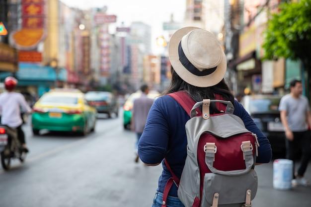 Азиатский backpacker путешествовать в продовольственном рынке улицы дороги yaowarat в бангкоке, таиланде.