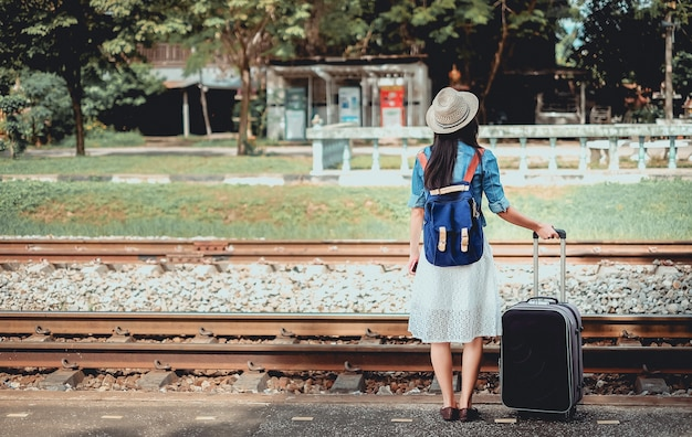 Backpacker young girl have baggage waiting for train at  train station.