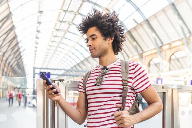 Счастливый человек с помощью телефона на вокзале в лондоне - молодой человек смешанной расы с вьющимися волосами, улыбаясь и набрав на телефоне, ждет поезд - backpacker путешествия и образ жизни