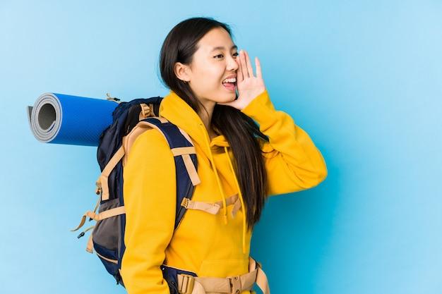 Молодая китайская женщина backpacker изолировала кричать и держать ладонь около раскрытого рта.