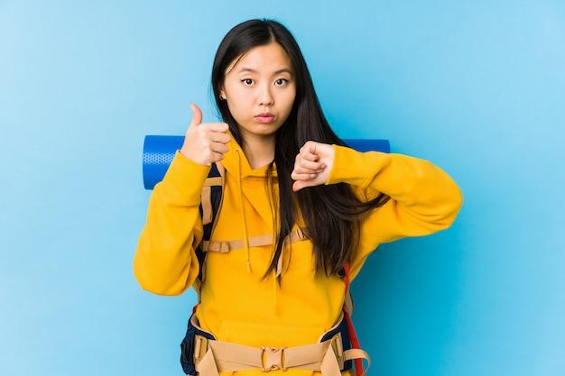 Молодая китайская женщина backpacker изолировала показывать большие пальцы руки вверх и большие пальцы руки вниз, трудно выбирает концепцию