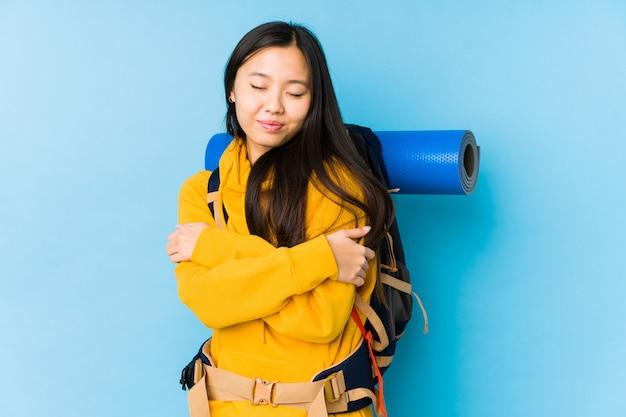 Молодая китайская женщина backpacker изолировала объятия, усмехаясь беззаботный и счастливый.