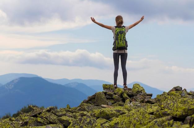 Задний взгляд девушки молодого тонкого backpacker туристской при поднятые оружия стоя на скалистой верхней части против яркого голубого неба утра наслаждаясь туманной панорамой горной цепи. концепция туризма, путешествий и скалолазания.