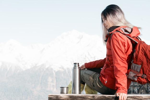 Backpacker женщина отдыхает зимой.