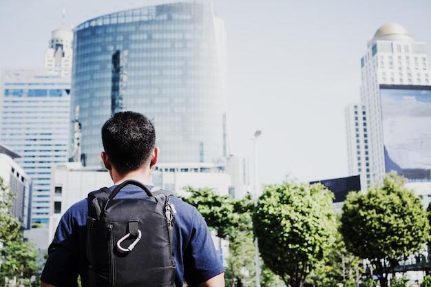 Backpacker путешественника молодого человека азиатский смотря город внешний в бангкоке, таиланде.