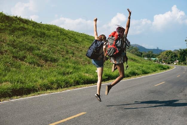 Разнообразные backpacker женщины прыжки на улице
