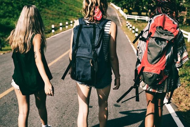 Разнообразные женщины backpacker гуляя вдоль стороны улицы