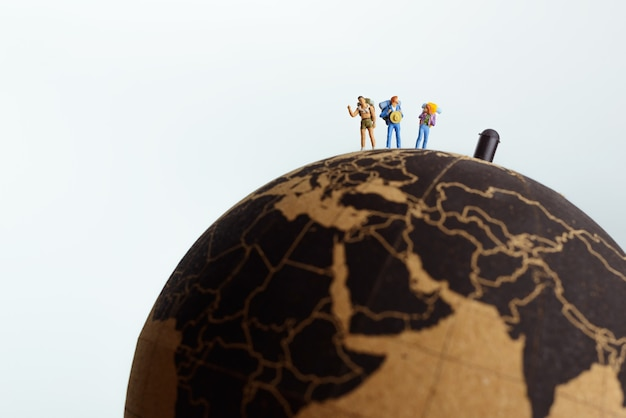 Backpackers on top of a globe