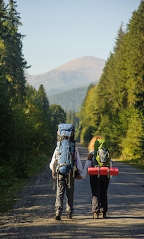 Backpackers walking on mountain road with backpacks