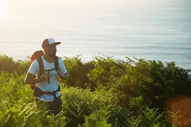 海の近くの丘でのバックペーカーハイキング