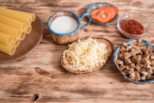 イタリア料理のコンセプト。パスタを調理するための材料。乾燥カネロニパスタ、チェリートマト、新鮮なバジル、黒backraundのニンニク。