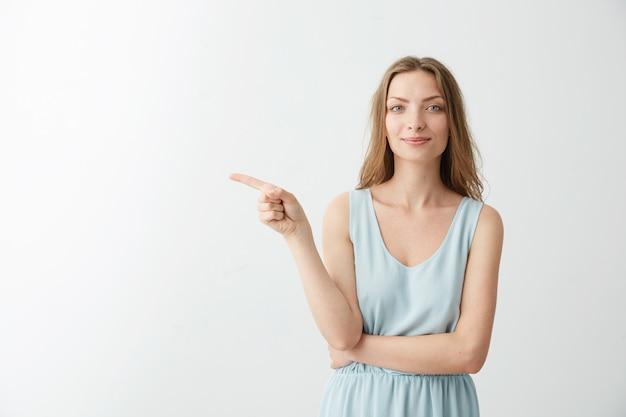 白いbackrgoundの側で人差し指を笑っている美しい陽気な少女。