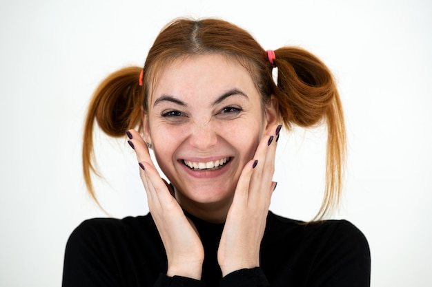 Портрет крупного плана смешного рыжеволосого девочка-подростка с ребяческой прической усмехаясь счастливо изолированный на белом backround.