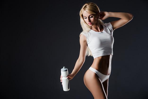 暗いbackroundに対して立っているボトルとスポーツウェアを着ている若い女性の写真。ショット