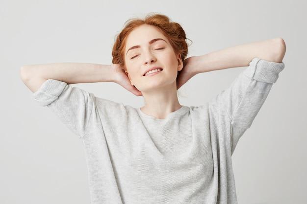 白backroundを楽しんで笑って目を閉じて美しい赤毛の若い女の子の肖像画。頭の後ろに手。