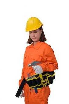 オレンジ色の防護服を着て、白いbackroundで分離されたツールベルトとハンマー手持ち株ヘルメットを身に着けている建設労働者