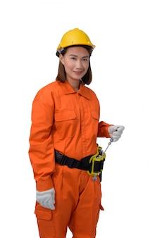 オレンジ色の保護服、白いbackroundで分離されたツールベルト付きドライバーを持っているヘルメット手身に着けている建設労働者