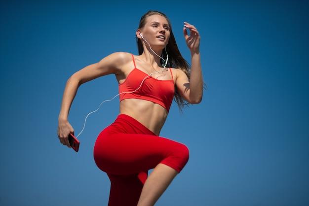 空backroundで走っている若いフィットネス女性。健康的なライフスタイルのコンセプト