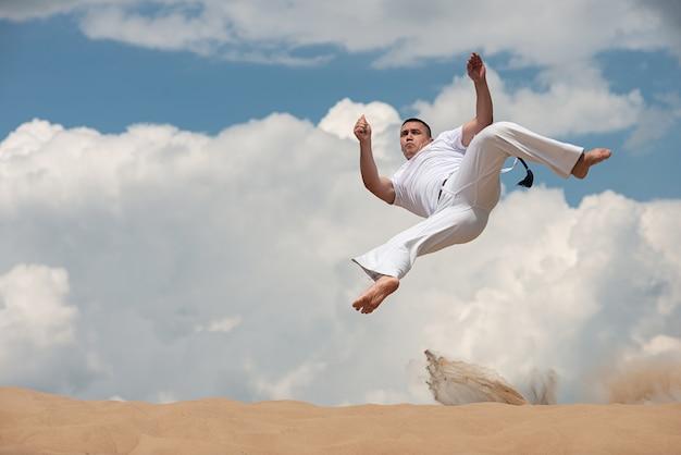若い男は空backroundでカポエイラを訓練します。男性がジャンプで格闘技を行う